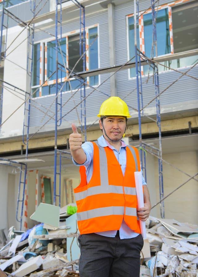 Asiatischer Vorarbeiterdaumen oben an der Baustelle stockbilder