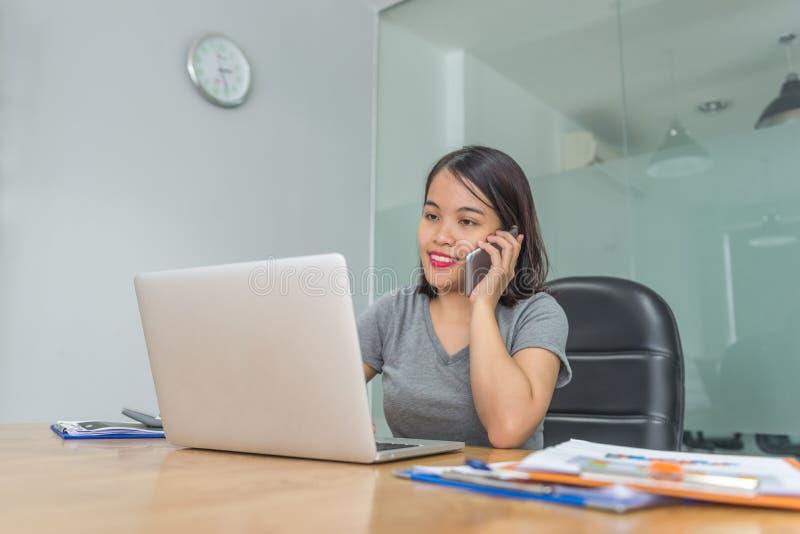 Asiatischer weiblicher antwortender Telefonanruf im Büro stockfotografie