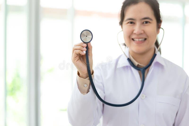 Asiatischer weiblicher Arzt im Hausmantelholdingstethoskop in der Hand am Krankenhaus, Arzt, der durch Stethoskop hört lizenzfreie stockfotografie