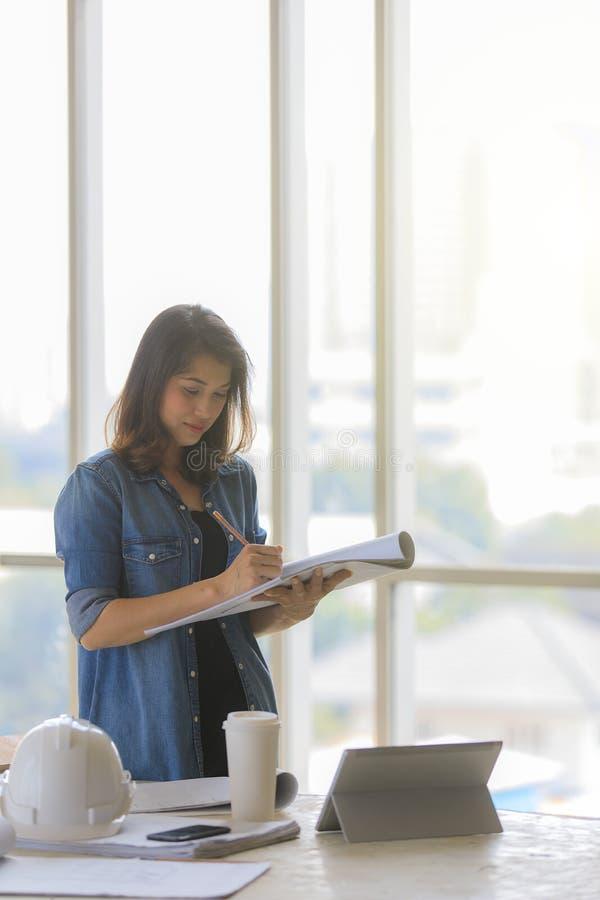 Asiatischer weiblicher Ingenieur in der Blue Jeans-Hemdstellung in der Baustelle mit weißem Sturzhelm lizenzfreie stockfotos