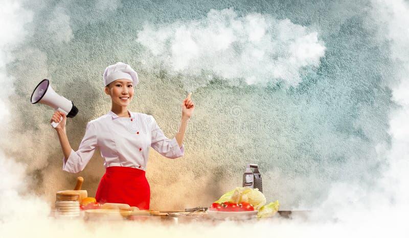 Asiatischer weiblicher Koch, der Megaphon anhält stockbild