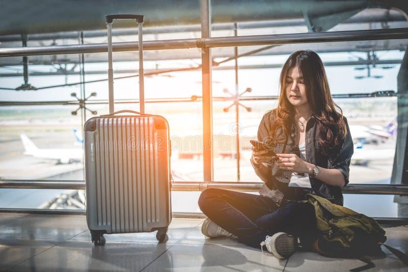 Asiatischer weiblicher Reisender, der intelligentes Telefon für PrüfungsFlugzeit verwendet stockfoto