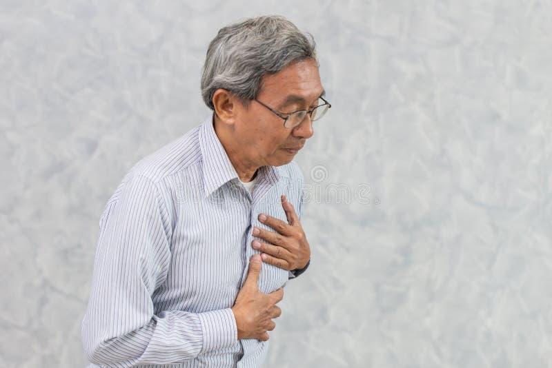 Asiatisches Ältestes leiden unter Schmerz in der Brust vom Herzinfarkt stockbild