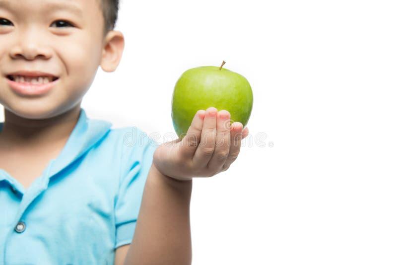 Asiatisches Baby, das den roten Apfel, lokalisiert auf Weiß hält und isst stockbild