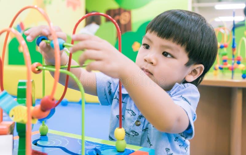 Asiatisches Baby, das mit pädagogischem Spielzeug spielt lizenzfreie stockfotos