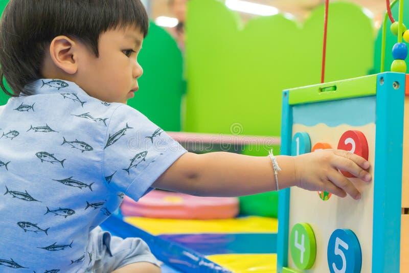 Asiatisches Baby, das mit pädagogischem Spielzeug spielt stockfotografie
