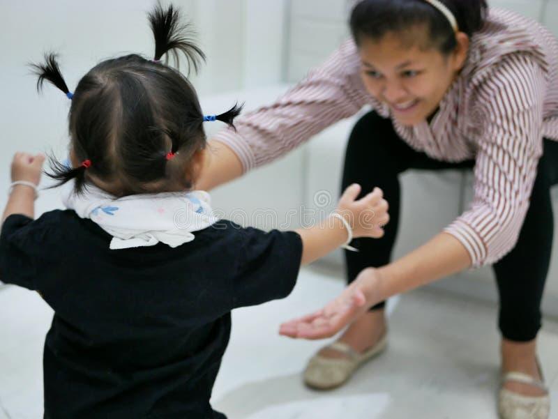 Asiatisches Baby, das in Richtung zu ihrer Mutter, während die Mutter vorwärts sich lehnt mit den Händen heraus erreichen bereite lizenzfreie stockbilder
