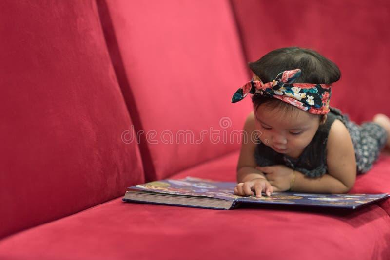Asiatisches Babykleinkind, das sich auf rotem Sofalesebuch hinlegt stockfotografie