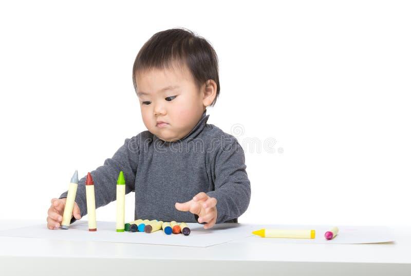Asiatisches Babyspiel mit Zeichenstift stockfotos