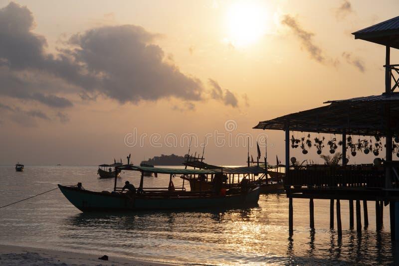 Asiatisches Boots- und Hausschattenbild auf orange Himmel Sonnenuntergangseelandschaftsfoto Sonnenaufgang auf Koh Rong-Insel stockfoto