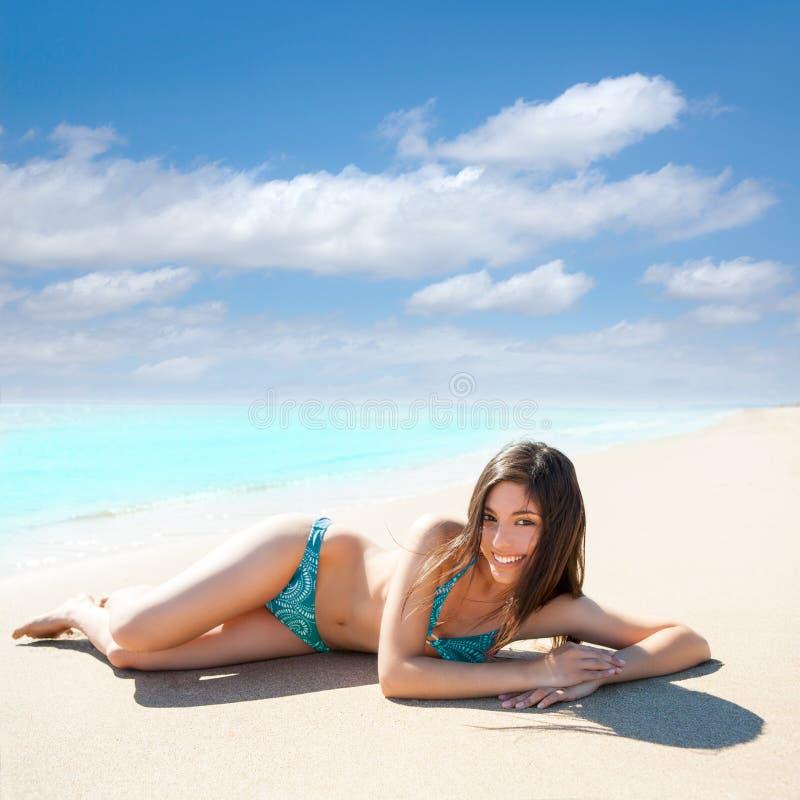 Asiatisches Brunettemädchen, das auf dem Sommerstrand-Weißsand liegt lizenzfreie stockbilder