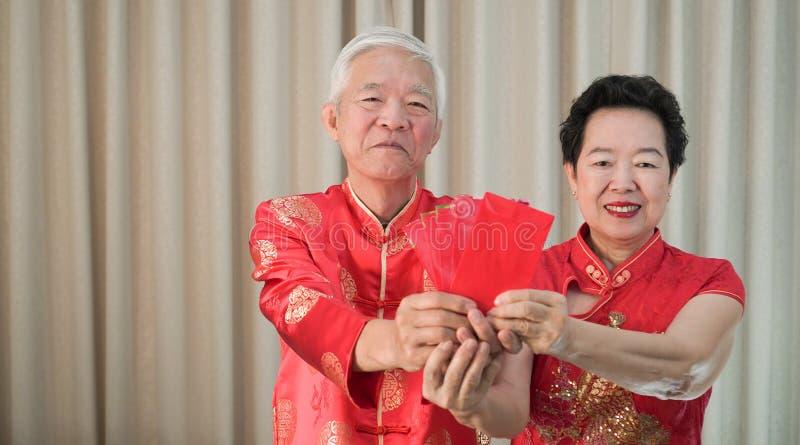 Asiatisches chinesisches älteres Rot des neuen Jahres der Paare glückliches Festival einschlagen stockfotografie