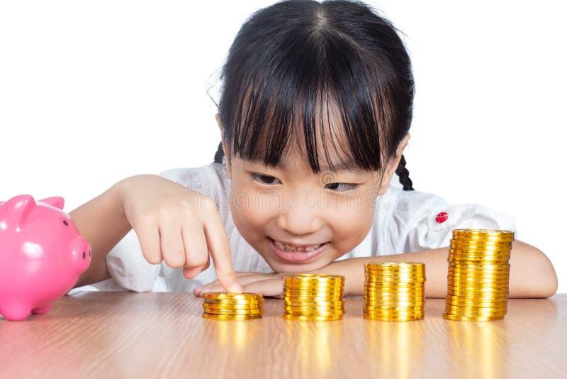 Asiatisches chinesisches kleines Mädchen, das mit goldenem Bitcoin spielt stockfotografie