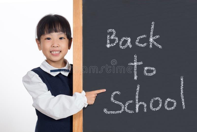 Asiatisches chinesisches kleines Mädchen, das neben Tafel steht lizenzfreies stockbild