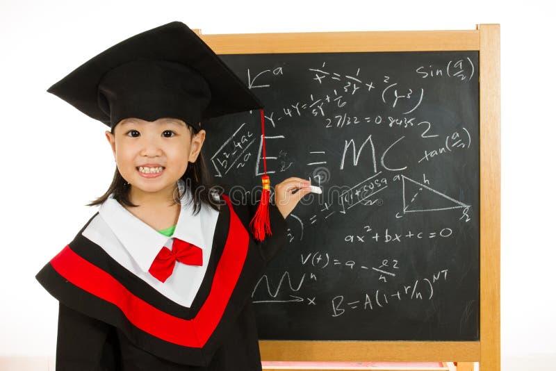 Asiatisches chinesisches kleines Mädchen in Staffelungskleid-againts Tafel lizenzfreie stockfotografie