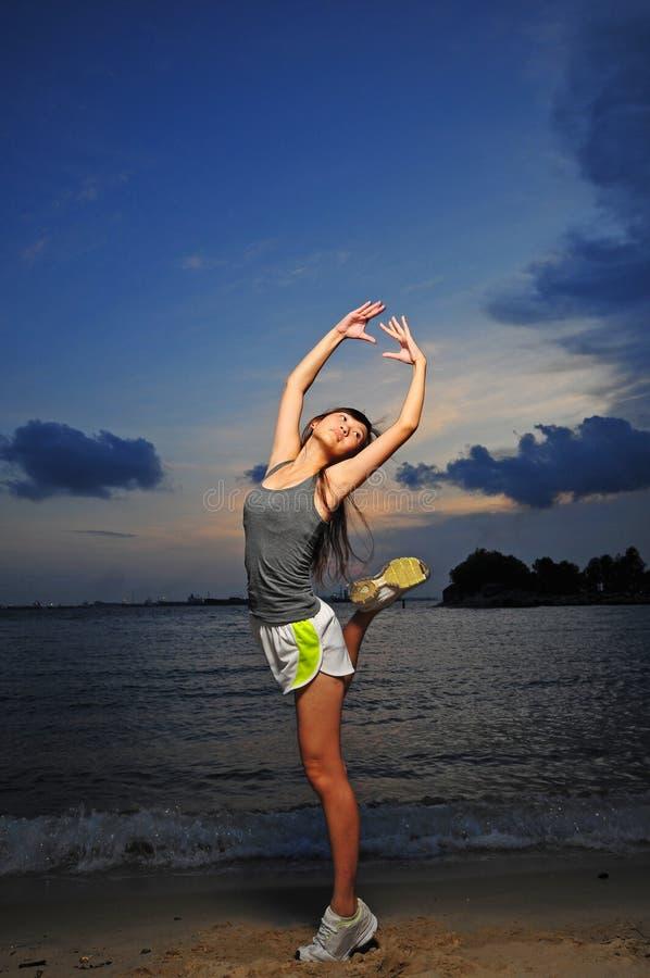 Asiatisches chinesisches Mädchen-übendes Ballett auf dem Strand stockfotografie