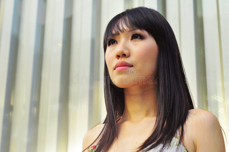 Asiatisches chinesisches Mädchen, das ernst schaut stockbild