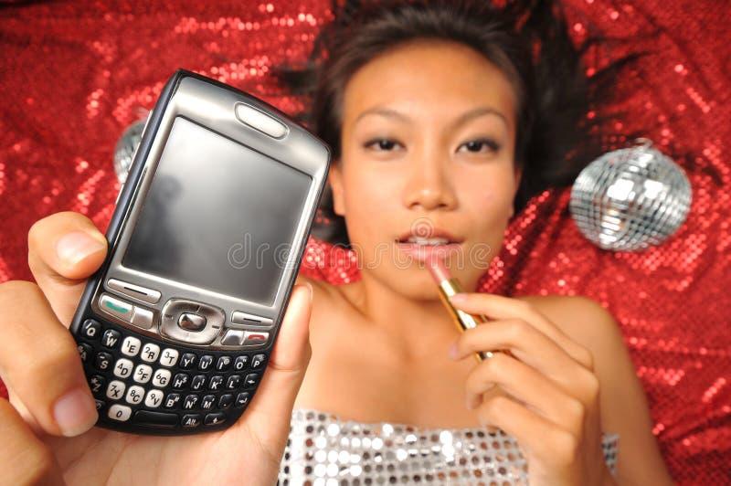Asiatisches chinesisches Mädchen, das Lippenstift setzt und Pferdestärken anhält lizenzfreie stockbilder