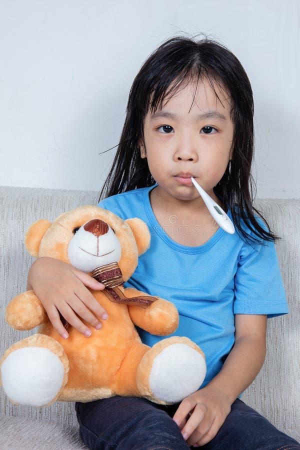 Asiatisches chinesisches Mädchen, das Teddybären für Fiebertemperatur meas hält stockfotografie