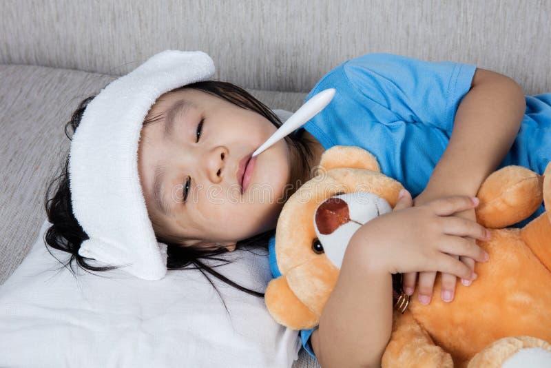 Asiatisches chinesisches Mädchen, das Teddybären für Fiebertemperatur meas hält stockbilder