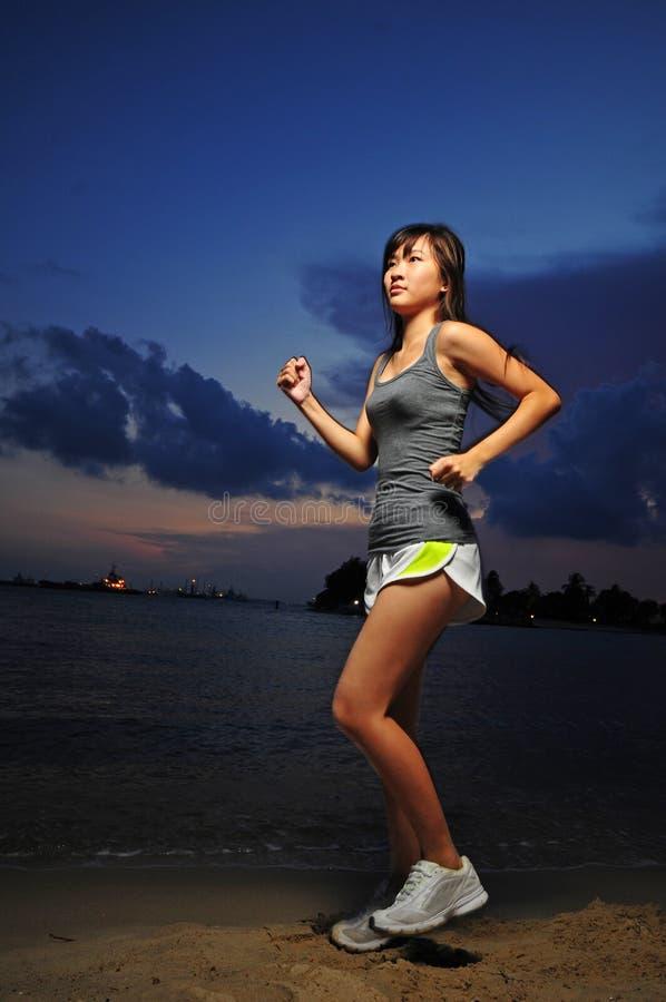 Asiatisches chinesisches Mädchen, das während des Sonnenaufgangs trainiert stockbild