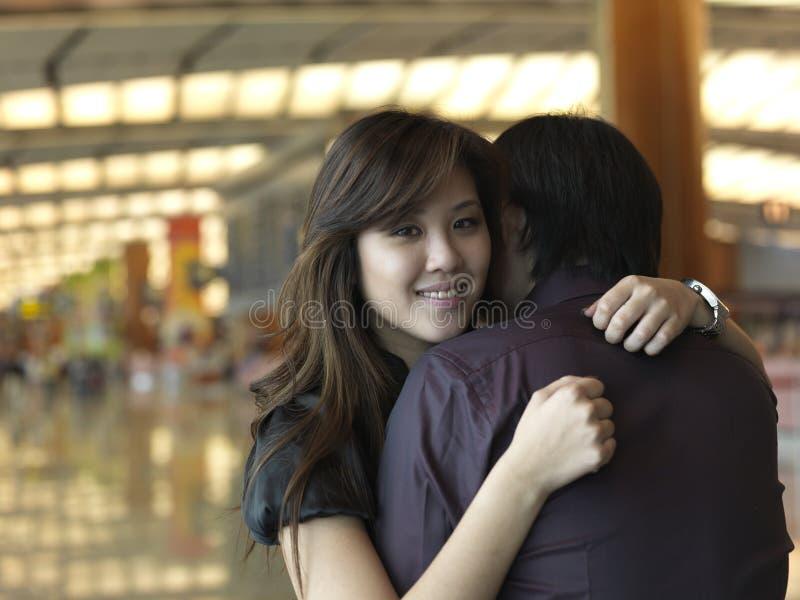 Asiatisches chinesisches Mädchen gegrüßt vom Kerl am Flughafen lizenzfreies stockfoto