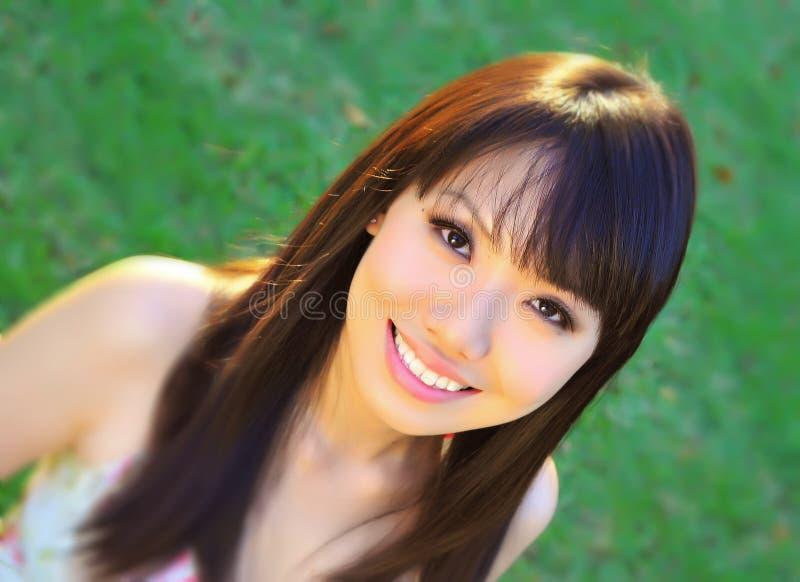 Asiatisches chinesisches Mädchen im grünen Park lizenzfreie stockbilder