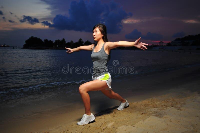 Asiatisches chinesisches Mädchen, welches das Ausdehnen auf den Strand tut lizenzfreie stockfotos