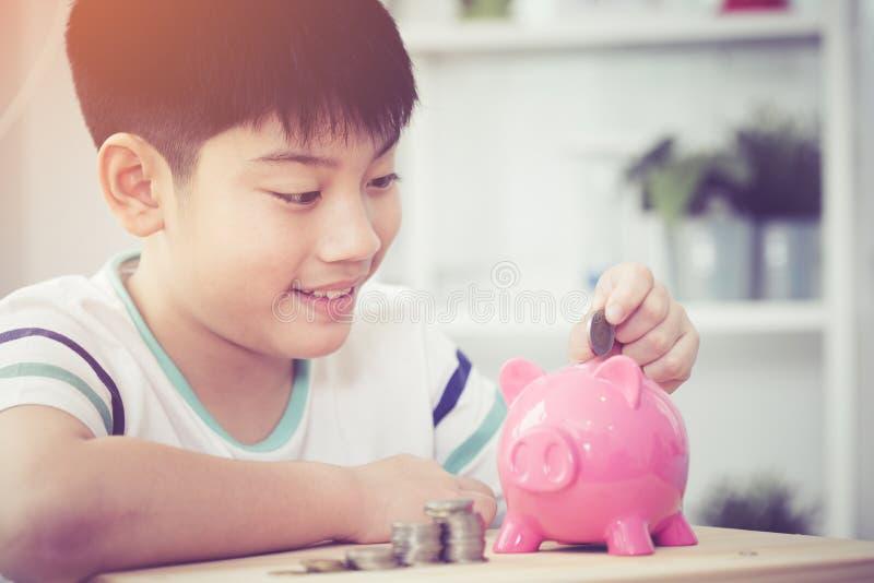 Asiatisches Einsparungsgeld des kleinen Jungen im rosa Sparschwein lizenzfreies stockbild