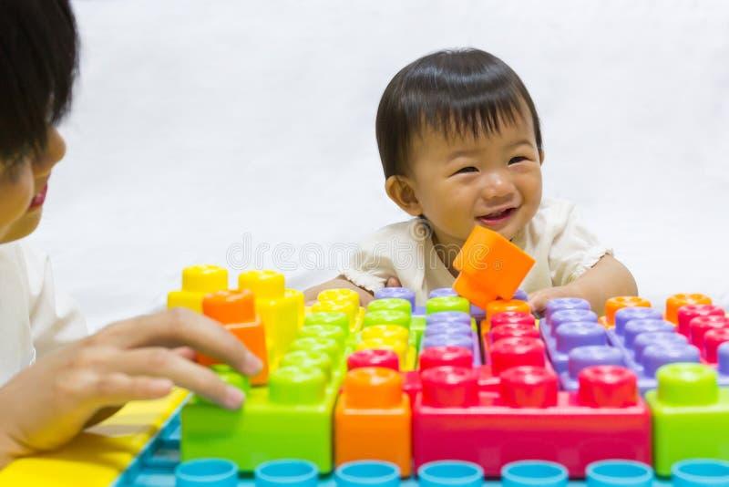 Asiatisches entzückendes Baby ein Jahr spielt zackiges Spielzeug für Kind lizenzfreies stockfoto