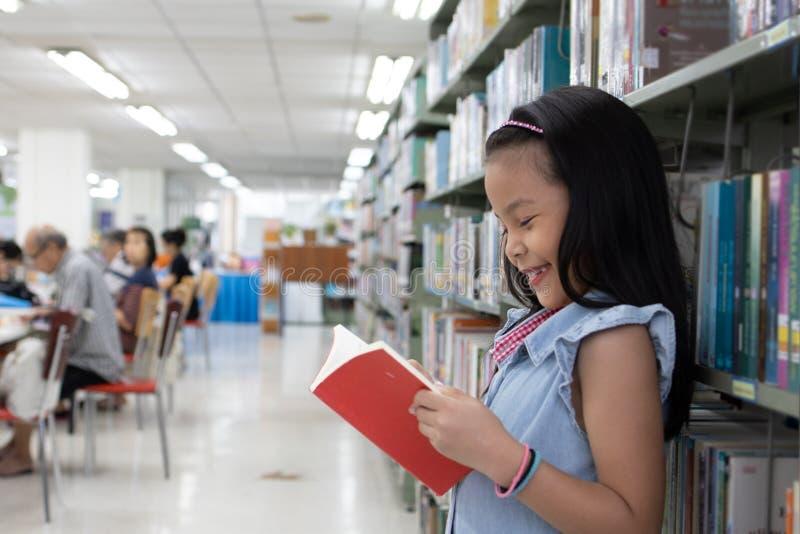 Asiatisches entzückendes Schulmädchen, das ein Buch und ein Lächeln liest stockbilder