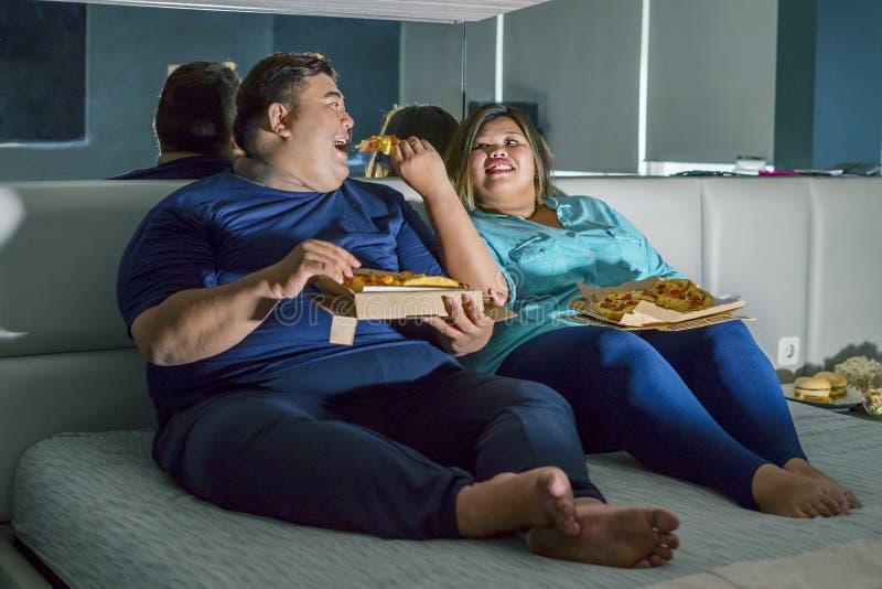 Asiatisches Fett, das romantisch Pizza isst stockbilder