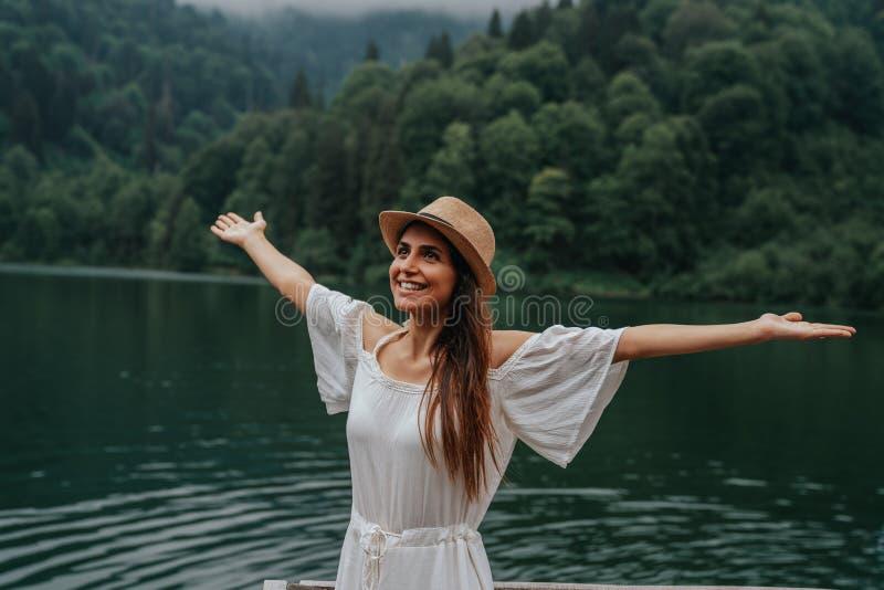Asiatisches Frauenlächeln glücklich am sonnigen Sommer- oder Frühlingstag draußen im Park durch See Lächeln der jungen Frau glück stockfotografie