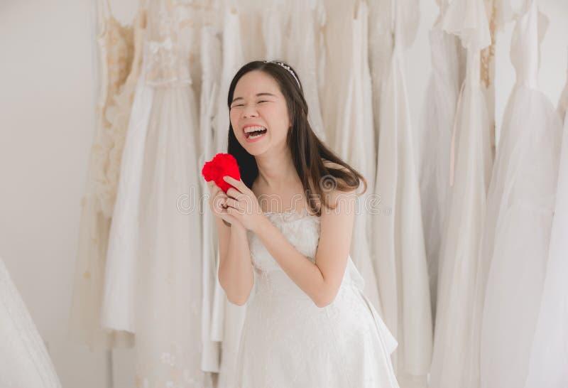Asiatisches Frauenlächeln und -hand der glücklichen jungen schönen Braut vorbildliches rotes Herz halten lizenzfreies stockbild