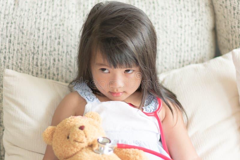Asiatisches freches nettes kleines Mädchen, das Doktor mit Stethoskop spielt lizenzfreie stockfotografie