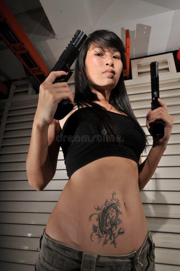 asiatisches Gangster-Mädchen, das zwei Gewehre anhält lizenzfreie stockbilder