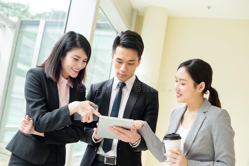 Asiatisches Geschäftsteam, das etwas auf Tablet-Computer spricht stockbild