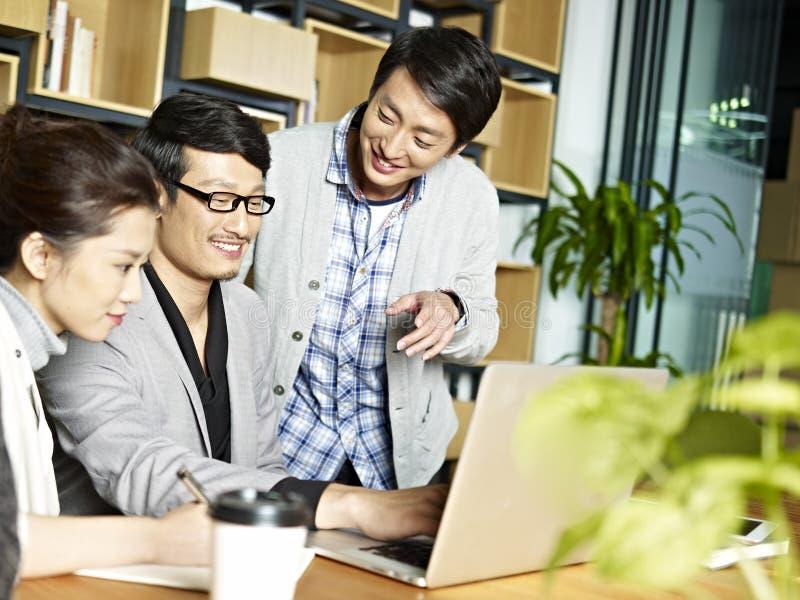 Asiatisches Geschäftsteam, das im Büro zusammenarbeitet stockbild