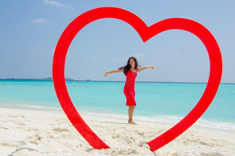 Asiatisches glückliches Mädchen in einem roten Kleid, das am tropischen Strand innerhalb des Herzens steht lizenzfreie stockfotografie