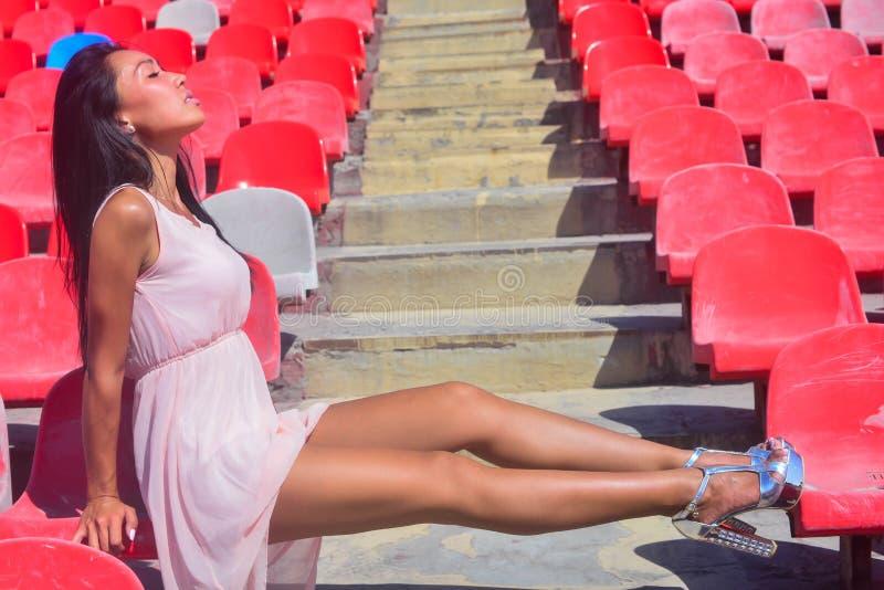 Asiatisches glückliches Modell, das am Stadion sitzt auf brigh aufwirft lizenzfreie stockfotografie