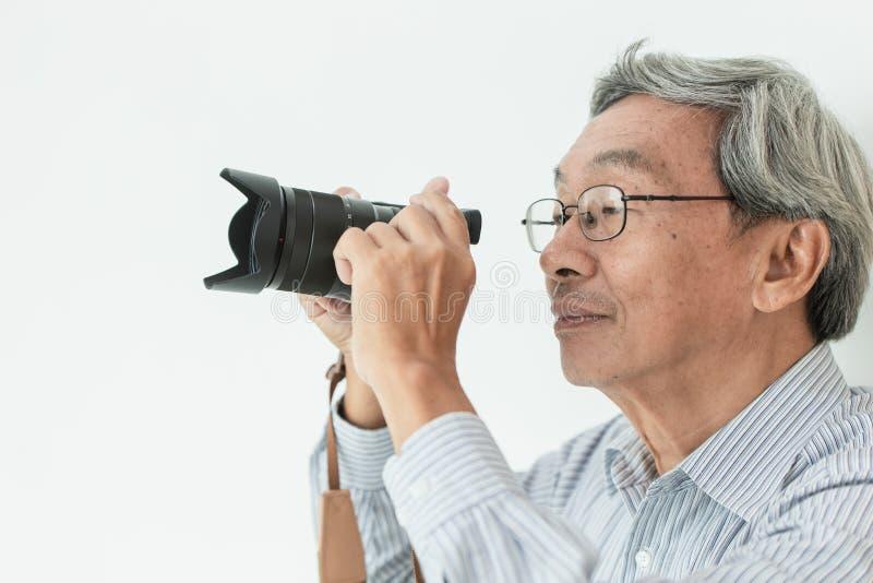 Asiatisches Glasruhestandshobby des alten Mannes als Fotograf nehmen eine Fotografie lizenzfreies stockbild