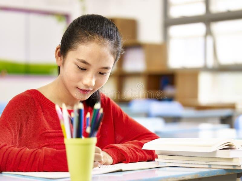Asiatisches grundlegendes Schulmädchen, das im Klassenzimmer studiert lizenzfreie stockfotografie