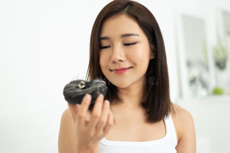 Asiatisches hübsches Mädchen, das Schokoladendonut isst stockfotografie
