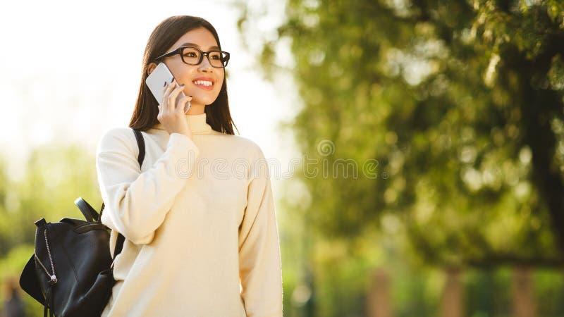 Asiatisches jugendlich Mädchen, das am Telefon, Bruch im College habend spricht lizenzfreie stockfotografie