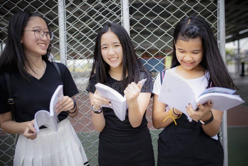 Asiatisches Jugendlichholdingschulbuch und Lachen mit dem Glückgefühl, das im Freien steht stockbilder