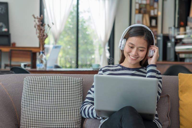 Asiatisches Jugendlichmädchen, das an Laptop-Computer und hörende Musik verwendet lizenzfreie stockfotos