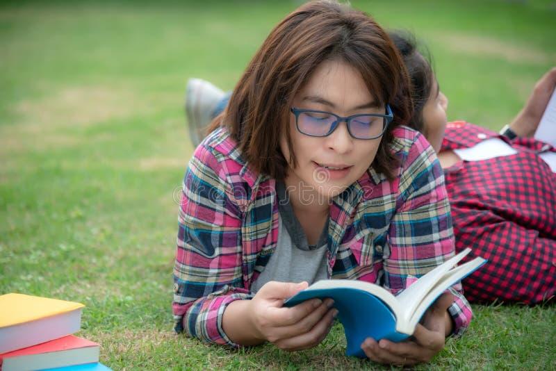 Asiatisches junge Frauen- und Freundlesebuch auf Gras draußen für Bildung lizenzfreie stockbilder