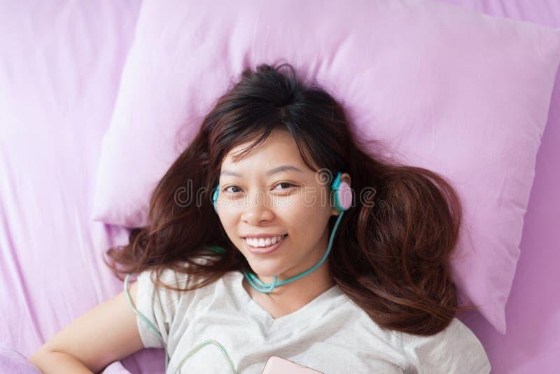 Asiatisches junges attraktives Mädchen, das auf Bettlächeln liegt stockfoto