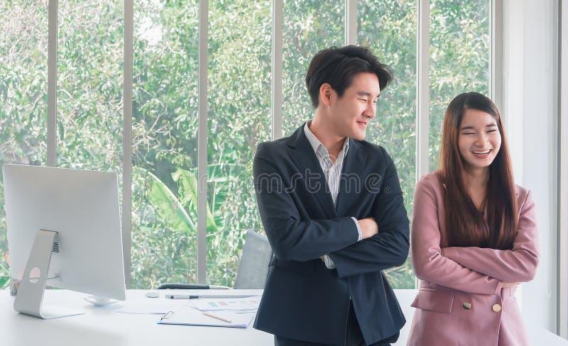 Asiatisches junges hübsches Geschäftsmanngespräch mit der schönen Geschäftsfrau so lustig lizenzfreies stockbild
