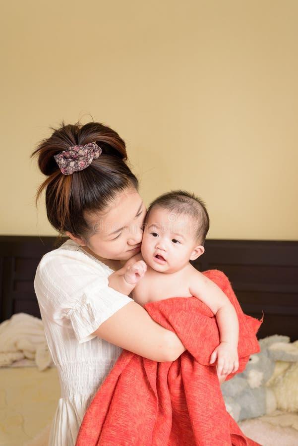 Asiatisches junges Muttergriffbaby stockfotografie